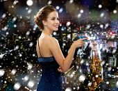 drinks, christmas, holidays and people concept - smiling woman in evening dress holding cocktail over snowy night city background