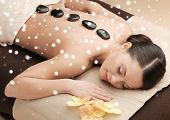 beauty, health, holidays, people and spa concept - beautiful woman in spa salon getting hot stones massage