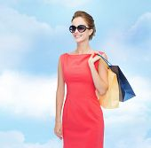 shopping, sale, christmas and holiday concept - smiling elegant woman in red dress and sunglasses with shopping bags