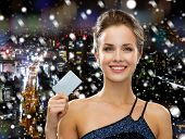 shopping, wealth, christmas, holidays and people concept - smiling woman in evening dress holding credit card over snowy night city background