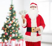 christmas, holidays, winning, currency and people concept - man in costume of santa claus with dollar money over living room with tree