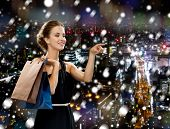 shopping, sale, christmas, people and holidays concept - smiling woman in evening dress with shopping bags pointing finger over snowy night city background