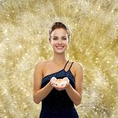 people, christmas, winter holidays and glamour concept - smiling woman in evening dress with diamond over yellow lights background