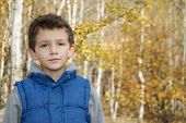 Little Smiling Boy In Autumn Forest.
