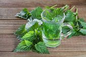 Tea with fresh nettles on a wooden background