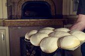 Fresh original Italian raw pizza dough,  stone oven in background.