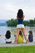 Mother and girls contemplating a lake