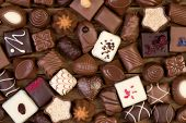 Assorted chocolate pralines on wooden background