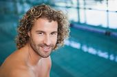 Close up portrait of a shirtless fit swimmer by the pool at leisure center