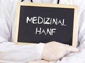 Doctor Shows Information On Blackboard: Medical Marijuana In German