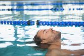 Close-up side view of a fit swimmer in the pool at leisure center