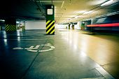 stock photo of parking lot  - Parking garage underground interior with car in motion blur - JPG