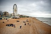 BRIGHTON - APRIL 06 - View down the golden sand of Brighton beachfront to the ferris wheel and amusement park with groups of people on the beach on April 06, 2014