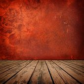 Red room. Red wall with grunge texture and rustic wooden floor in a surreal setting.
