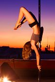 Young pole dance woman on urban background.