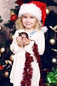 Cute Little Girl In Santa's Hat Decorating Christmas Tree