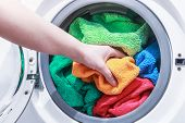 picture of dirty-laundry  - hand and puts the laundry into the washing machine - JPG