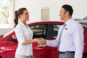 pic of handshake  - cheerful middle aged car dealer handshake with customer in showroom - JPG