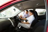 stock photo of showrooms  - car sales consultant showing a new car to potential customer in showroom - JPG