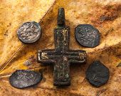 pic of copper coins  - medieval Christian cross Copper and silver coins on the background of dried leaves - JPG