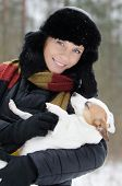 stock photo of jack russell terrier  - Young woman holding Jack Russell terrier in winter time - JPG