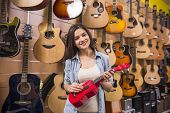 picture of ukulele  - Girl is playing on red ukulele in music shop - JPG