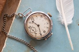 stock photo of politeness  - Retro background old watches on a blue background and feather vintage - JPG