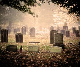 stock photo of tombstone  - Tombstone and graves in an ancient church graveyard - JPG