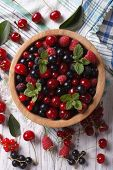 picture of blackberries  - Salad of cherry raspberry currant and blackberry in a wooden bowl on the table close - JPG