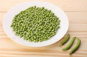 pic of green pea  - Green peas in white plate and pea pods on wooden tablecloseup - JPG