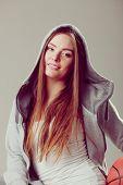 stock photo of hoods  - Sporty teenager girl wearing hooded sweatshirt holding basketball - JPG