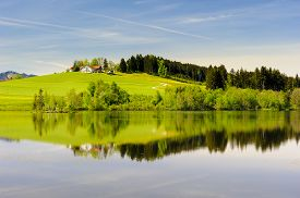 image of bavaria  - wide panorama landscape in Bavaria Germany with farm house in meadow mirroring in lake - JPG