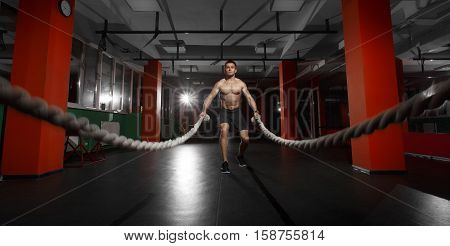 poster of Fitness man working out with battle ropes at gym. Battle ropes fitness man at gym workout exercise fitted body. Fitness man training with battle rope in fitness club. Training with battle rope