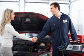 stock photo of auto garage  - Handsome mechanic and client woman in auto repair shop - JPG