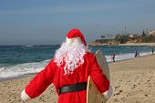 Surfing Santa. Santa Claus Surfs on his Surf Board while on a Beautiful Beach with a Blue Ocean. Foc poster