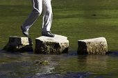 stock photo of stepping stones  - crossing three stepping stones in a river - JPG