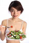 Smiling girl eating salad meal