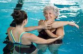 Young trainer helping senior woman in aqua aerobics. Senior retired woman staying fit by aqua aerobi poster