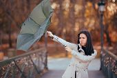 Girl Fighting The Wind Holding Umbrella Raining Weather poster