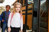 Elementary school girl and boy waiting to board the school bus poster