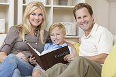 An attractive happy, young family of mother, father and son sitting on a sofa at home looking at a p