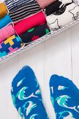 Box With Different Colorful Socks. Feet Selfie And A Socks Organizer On A White Wooden Background. T poster