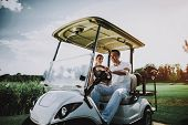 Happy Young Couple In White Cart On Golf Field. Young Family. Golf Club. Sports In Summer. Vehicle O poster