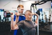 Senior man lifting weights with help of gym assistant. Work of personal trainer. Bodybuilding. poster