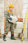 construction mason worker bricklayer lifting and installing calcium silicate brick