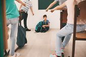Bullied boy sitting on floor in classroom poster