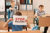 Little boy hiding behind sign Stop bullying in classroom poster