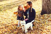 Mother, Daughter And Their Dog Having Fun In The Autumn Park Among The Falling Leaves. Walk In The A poster
