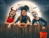 Happy brother and two sisters at Halloween. Funny kids in carnival costumes outdoors. Cheerful child poster
