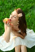 Adorable happy young lady with beautiful sappy apple over green grass